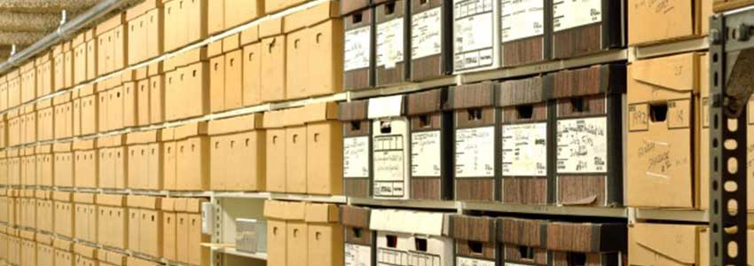 a row of metal shelves filled with archival boxes